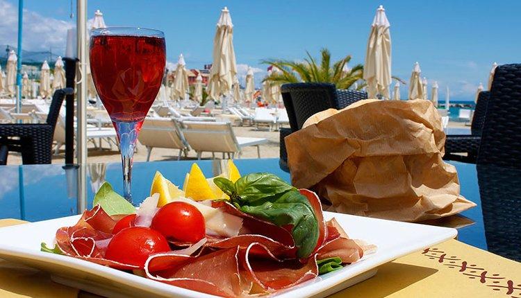 Geniet van de heerlijke Italiaanse prosciutto op het terras bij het zwembad van Hotel Garden Lido