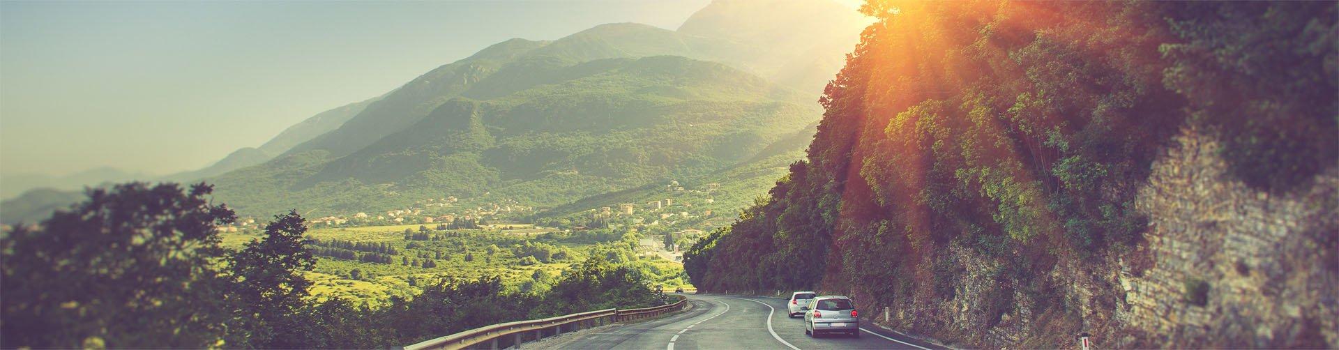 Rebel Travel - auto rijdt door de bergen bij een laag zonnetje