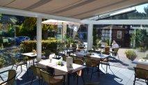 De serre van Parkhotel Flora kijkt mooi uit op de tuin