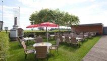 Het terras in de tuin van Hotel Weiss heeft een overdekt gedeelte en beschikt over een haard