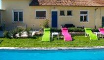 Het zwembad van Auberge des Moissons is voorzien van kleurrijke ligstoelen
